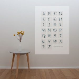 Botanical alphabet poster in black behind a table with flower vase on top