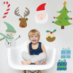 Happy and playful cute little two-year boy dressed in pajamas sitting on white chair in studio of photographer, raising his legs and posing. Children and happiness concept. Isolated shot, horizontal