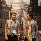 Two ladies standing in front of a black and white mural