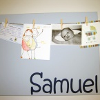 A pale blue board with cards and a photo pegged to it and the name Samuel on it