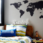 World Map removable Wall Mural behind a bed with a child name Kristof on the head rest