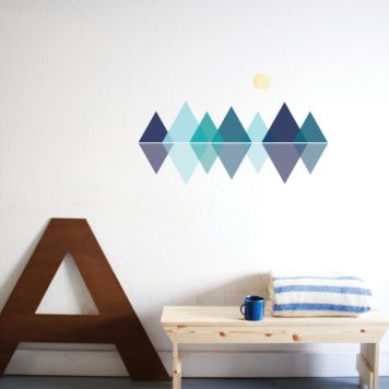 Paige Russell Mountain Range removable wall stickers behind a table with towel and mug on top