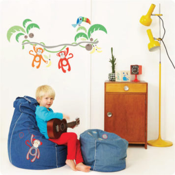 Jungle Canopy Removable Wall stickers with a boy in front sitting on a bean bag while playing a guitar