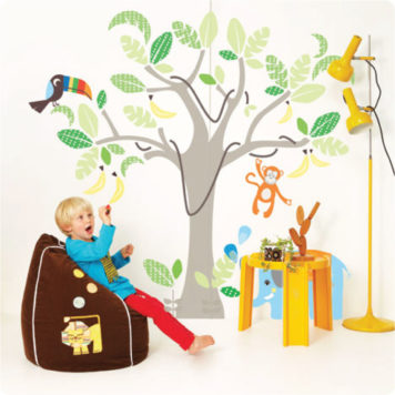 Jungle wall stickers with a boy in front sitting on a bag