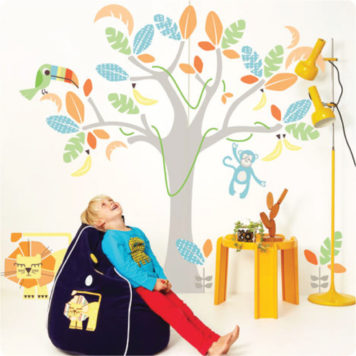 Jungle Land Removable Wall stickers with a boy in front sitting on a bean bag looking above