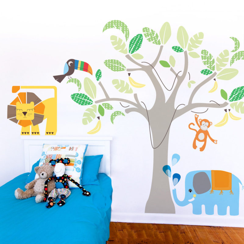 Jungle land removable wall stickers Cocoon Couture behind a blue child's bed