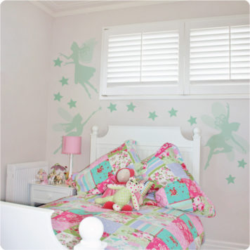 Pretty fairies removable wall stickers in mint behind a white bed and white side table