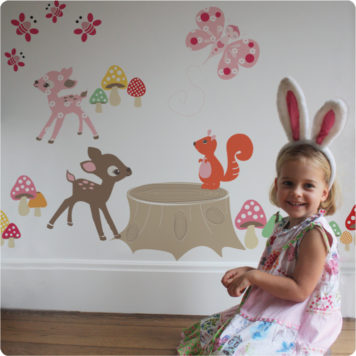 Enchanted Wood removable wall stickers by Cocoon Couture with a smiling girl sitting infront