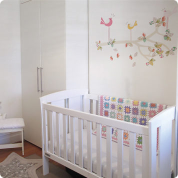 Enchanted Branch removable wall stickers by Cocoon Couture behind the crib