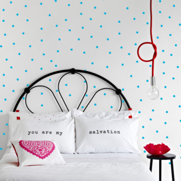 Salvation Jane Spots removable wallpaper Australia behind a bed and side table