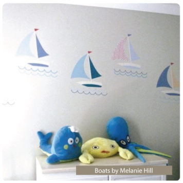 Boats removable wall stickers behind a cabinet with stuffed toys on top