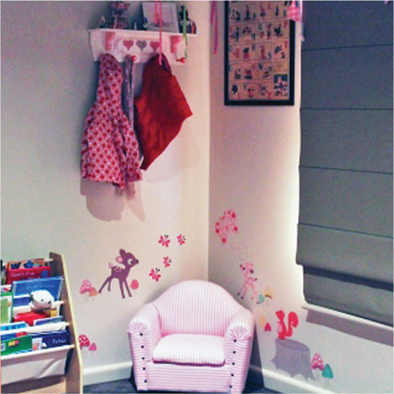 Enchanted Wood removable wall stickers by Cocoon Couture behind a pink sofa