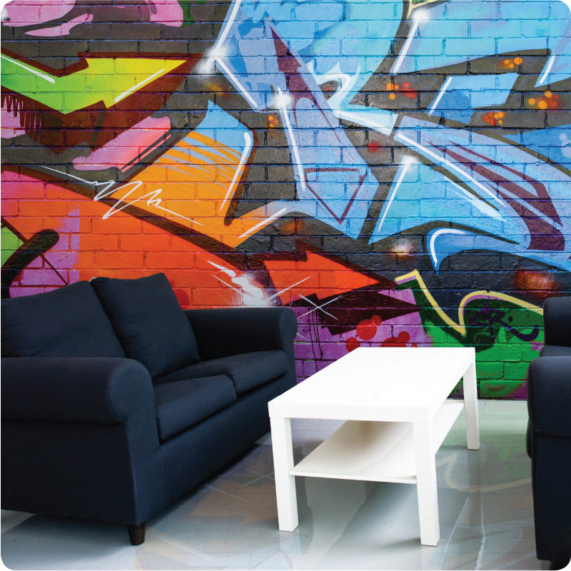 Graffiti removable wallpaper Australia behind a dark blue sofa and center table