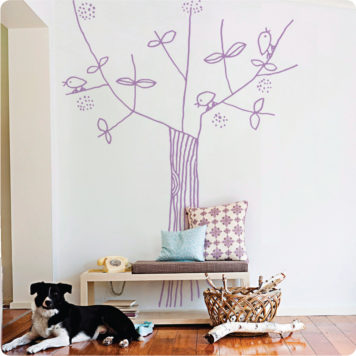Tree and Bird removable wall stickers by Jane Reiseger a cabinet with telephone and pillows on top