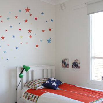 Stars removable wall stickers for childrens rooms behind a bed