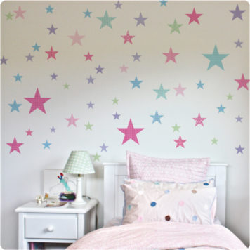 Stars removable wall stickers for childrens rooms behind a white bed and white side table