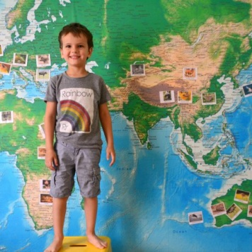 Detailed World Map Removable Wall Mural with a little boys standing in front and photos stuck on