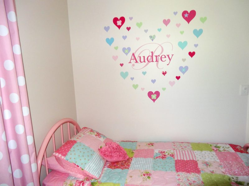 A girls bedroom with her name and hearts decorate the wall in stickers