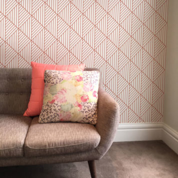 Geometric wallpaper in pink behind a small couch