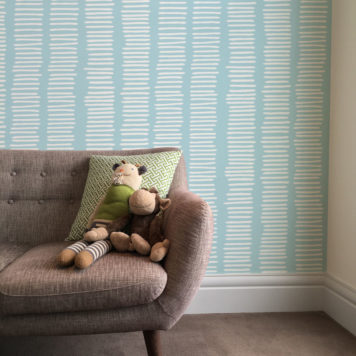 Lines wallpaper in blue and white behind a sofa