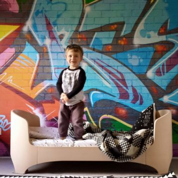 Little boy stands on his bed in front of a wall with graffiti on it