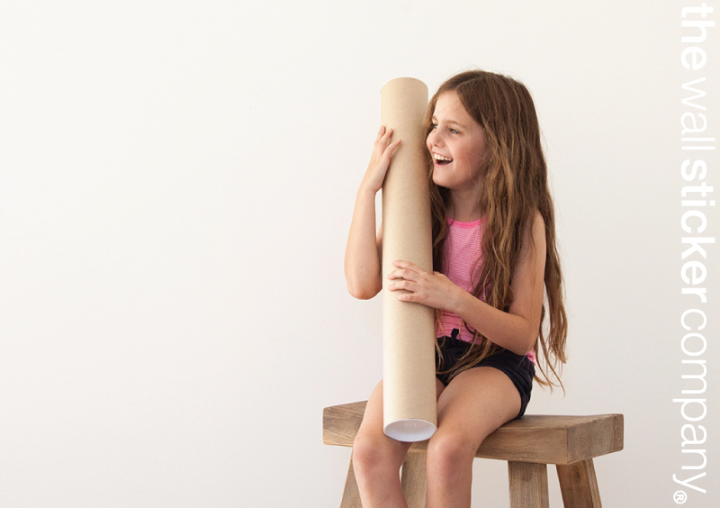 A little girl sits on a stool cuddling a tube and smiling