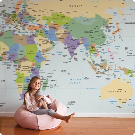 A little girl sitting on a beanbag in front of a World Map removable mural