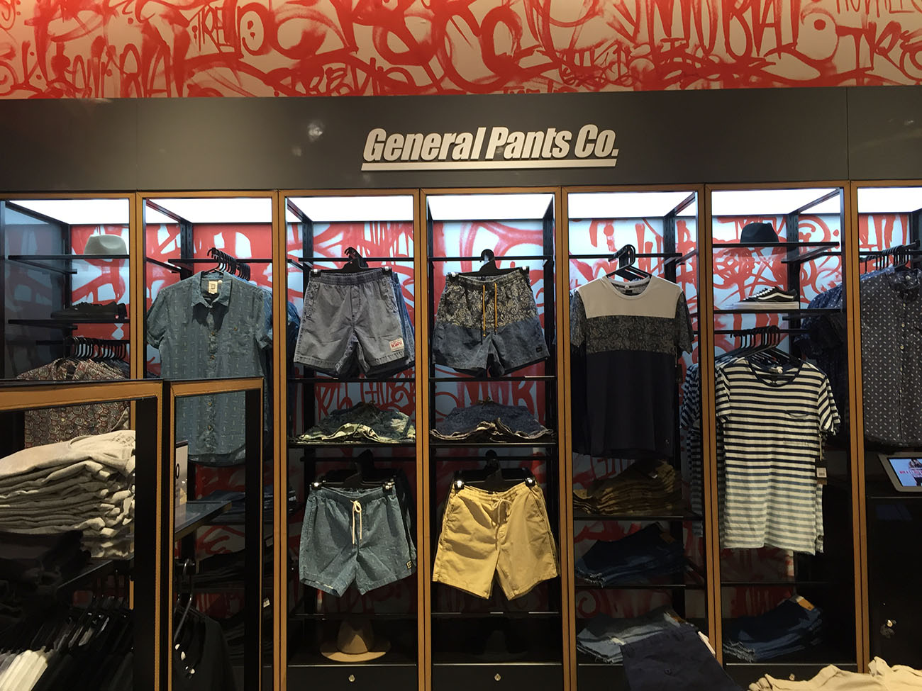 Clothes in a store with graffiti wall behind