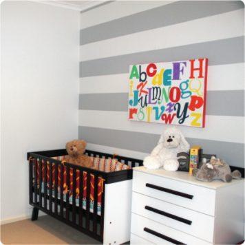 grey striped wallpaper in a nursery with wall art