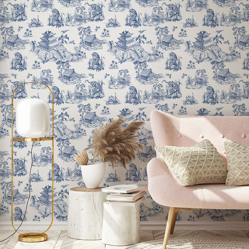 ASian toile wallpaper behnd a pink sofa