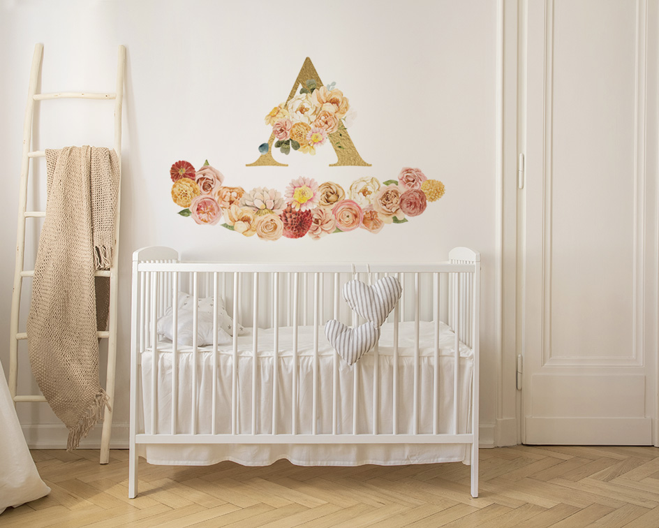 The letter A with flower wall stickers above a cot